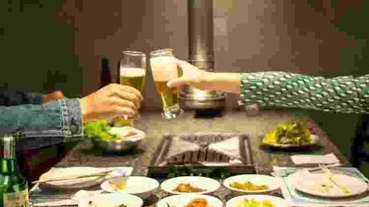 Churrasqueira no centro da mesa: confraternização é ponto chave do churrasco coreano - New Shin la Kwan/Reprodução - New Shin la Kwan/Reprodução