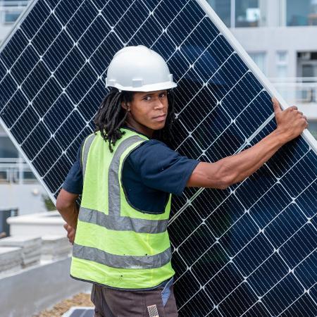 Um homem africano (segundo banco de imagens) instalando painéis solares - iStock