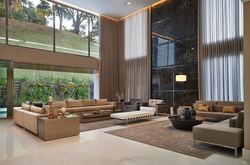 No espaçoso living da residência Hibiscos, a parede (à dir.) revestida com mármore marrom imperial se sobressai. Os móveis de linhas retas e atemporais (Líder Interiores), assim com a iluminação decorativa (Abatjour de Arte) preenchem o ambiente projetado pela arquiteta Estela Netto