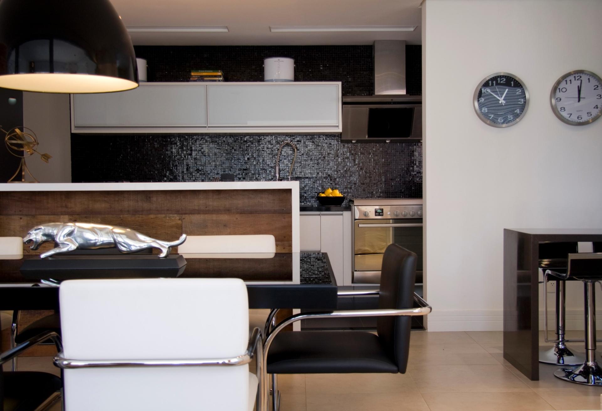 Os móveis planejados (Todeschini) contrastam com as pastilhas de vidro da (Vidrotil), na cozinha integrada deste apartamento duplex com 170 m². Esses materiais combinados aos eletrodomésticos em aço inox resultam na atmosfera moderna. O projeto é uma criação da arquiteta Karina Korn