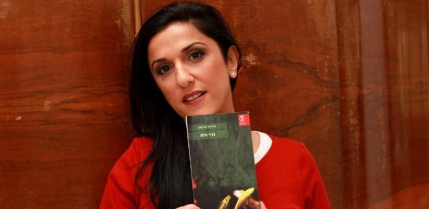 "31.dez.2015 - A escritora israelense Dorit Rabinyan posa com seu romance ""Uma Barreira Viva"""