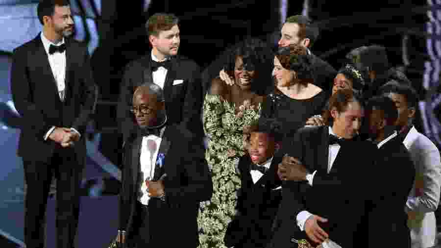 """Barry Jenkins, diretor de """"Moonlight"""", segura a estatueta de melhor filme à frente de Jimmy Kimmel e ao lado da produtora Adele Romanski - Lucy Nicholson/Reuters"""