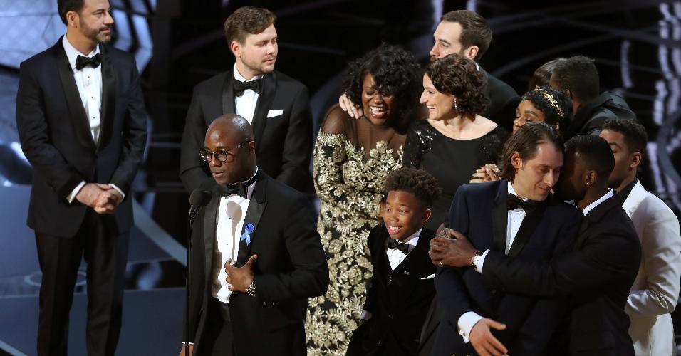 """Barry Jenkins, diretor de """"Moonlight"""", segura a estatueta de melhor filme à frente de Jimmy Kimmel e ao lado da produtora Adele Romanski"""