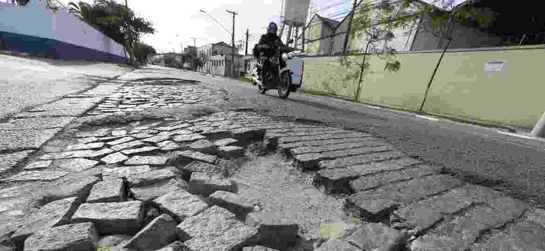 Moto passa por avenida desnivelada, esburacada e parcialmente asfaltada em São Paulo (SP): e o perigo de cair? - Robson Ventura/Folhapress
