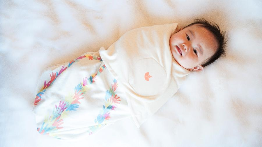"""Bebê usando """"swaddle"""" ou cueiro, que mantém o bebê aquecido e ajuda na qualidade do sono da criança - Divulgação"""