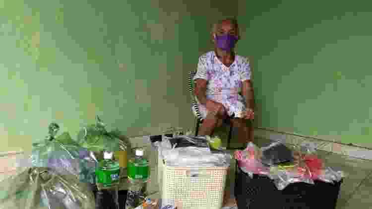 Vestindo máscara, dona Bernarda em frente a outras que costurou com a ajuda de nove amigas - Arquivo Pessoal
