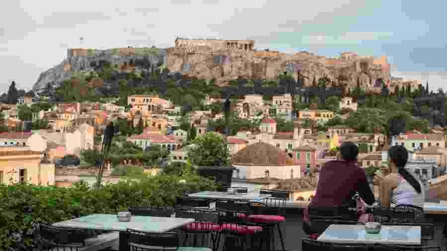Visitantes se sentam nas mesas de café em Monastiraki, na Grécia - Socrates Baltagiannis/picture alliance via Getty Images