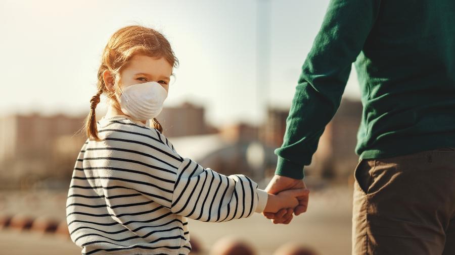 Criança com máscara andando em cidade grande - evgenyatamanenko/Getty Images/iStockphoto