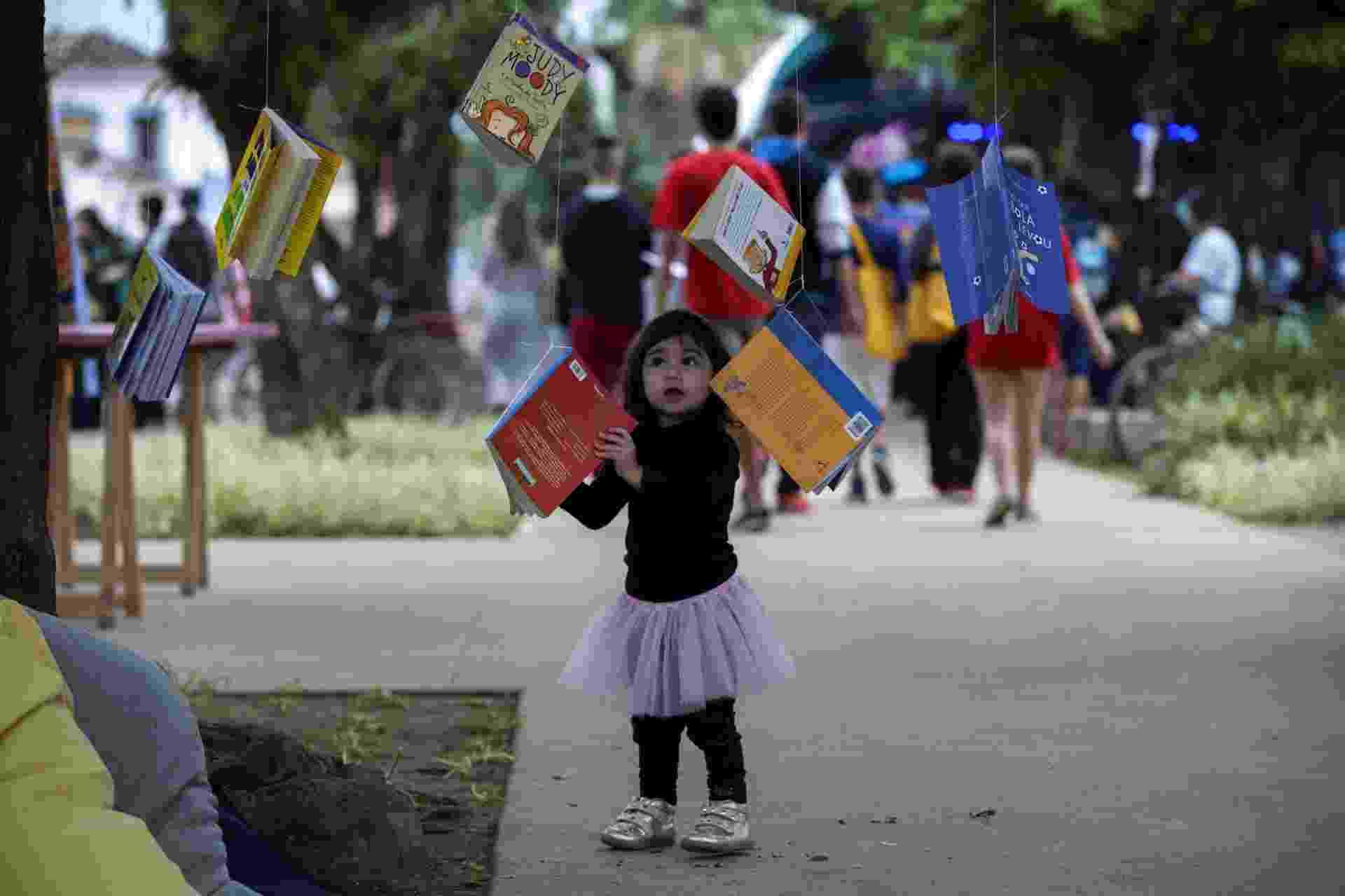 3.jul.2015 - Criança observa livros amarrados nas árvores na praça da Matriz, centro de Paraty, durante a 13ª edição da FLIP 2015 - EFE/Sebastião Moreira
