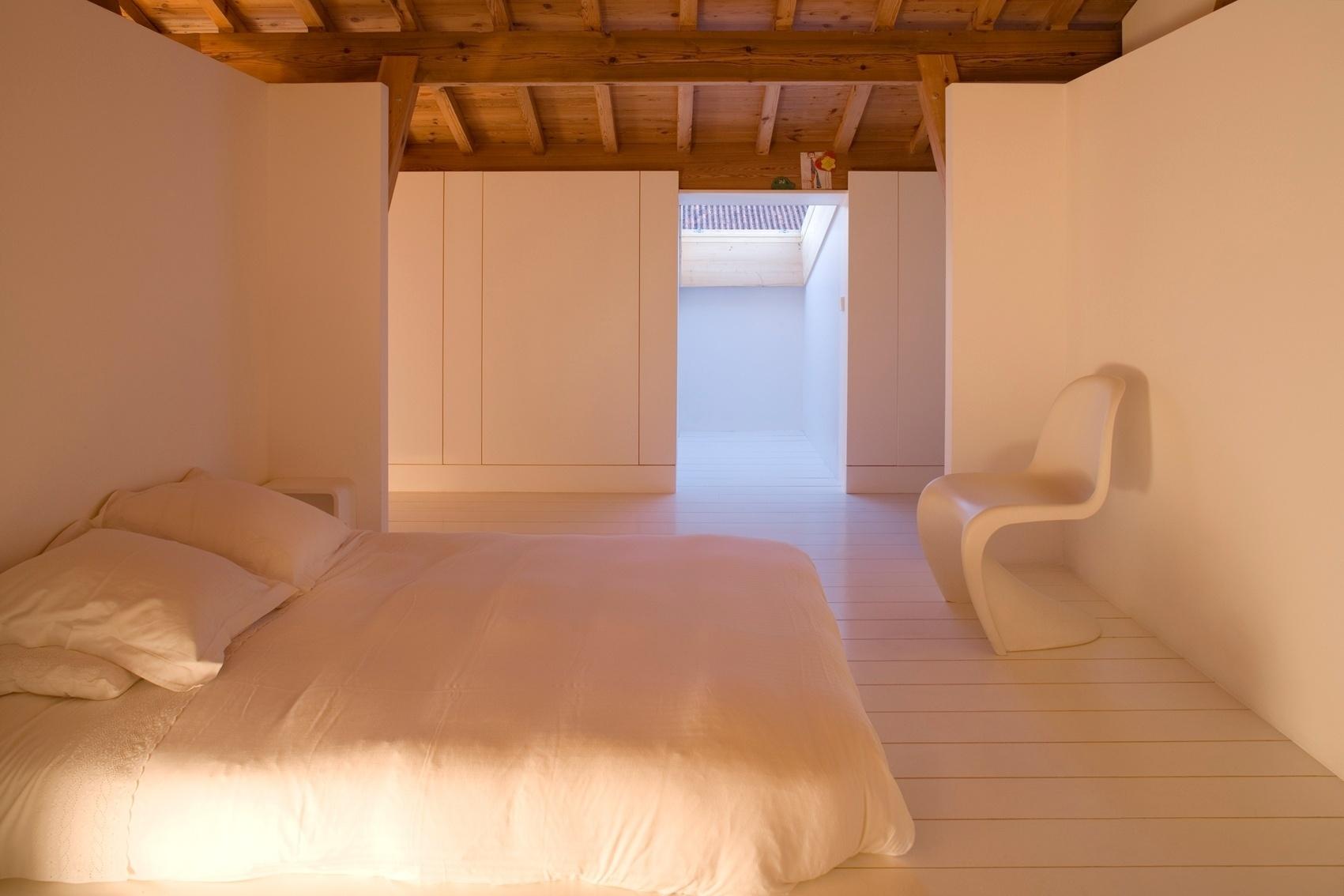 Os dormitórios recebem luz natural por aberturas no telhado ou através de janelas de mansarda. O estilo é bastante minimalista e o branco serve, também, para refletir a luz natural e melhorar a iluminação dos ambientes desenvolvidos pelo Atelier Bugio