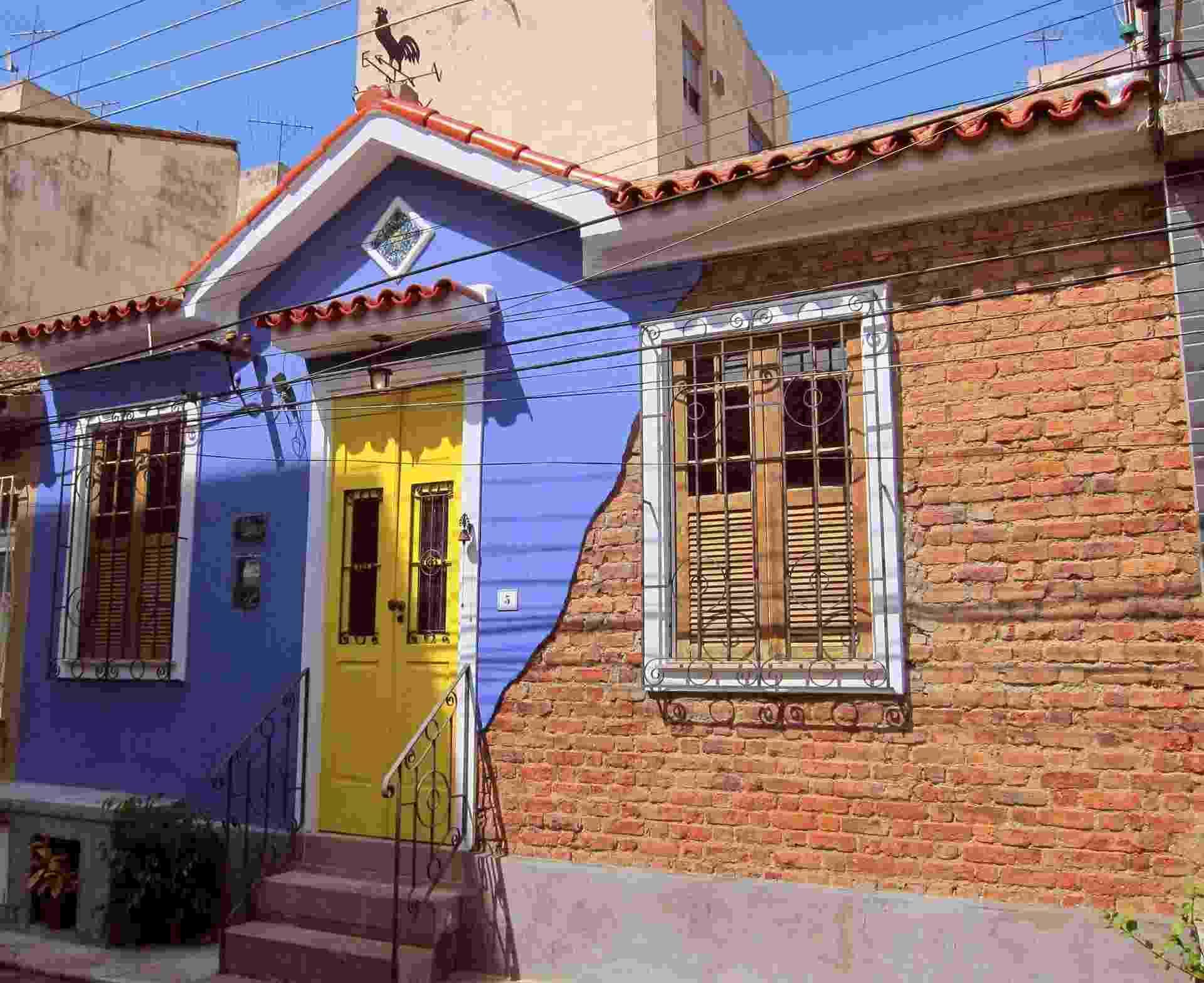 """A simpática casinha de 1936 passou por uma grande reforma, sem ter sua arquitetura descaracterizada. Os tijolos maciços ficaram à vista e contrastam com o reboco arroxeado e a porta amarela. """"O desenho do corrimão foi inspirado no gradil das portas e janelas, que são originais. E para completar a 'vibe' retrô, instalamos um galo de vento no telhado"""", conta a designer Paula Garrido - Divulgação"""