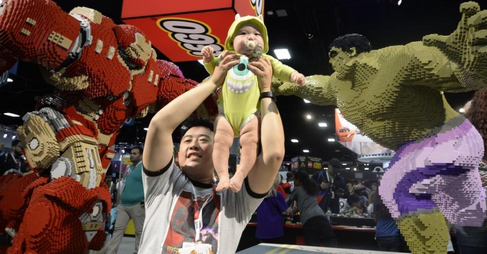 9.jul.2015 - Jerry Lee com seu filho, Dylan Lee, de apenas sete meses, ao lado das esculturas de Lego do Homem de Ferro e Hulk