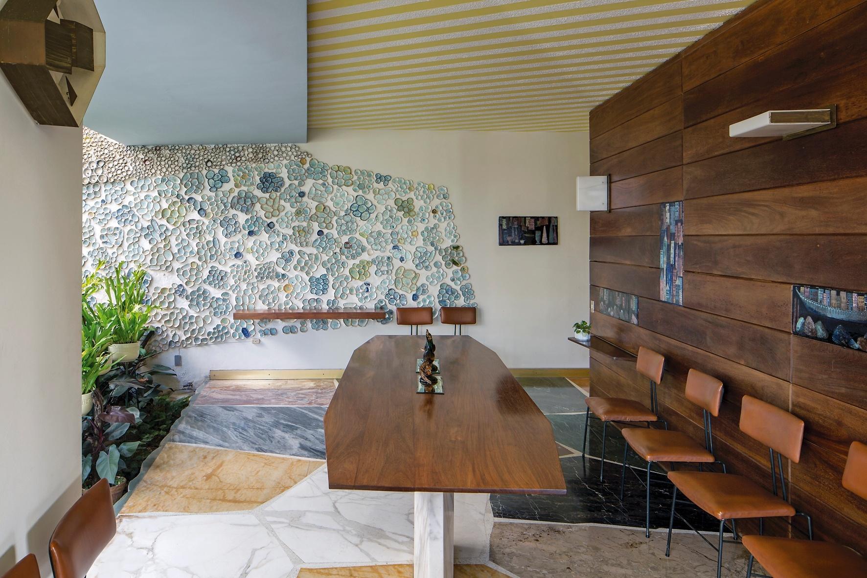 O pátio interno da Villa Planchart em Caracas mostra a habilidade de Gio Ponti para harmonizar materiais com cores e texturas diferentes e obras de arte, como o painel cerâmico (ao fundo), do artista-plástico italiano Fausto Melotti. No ambiente, uma grande mesa de jantar de madeira com base de mármore