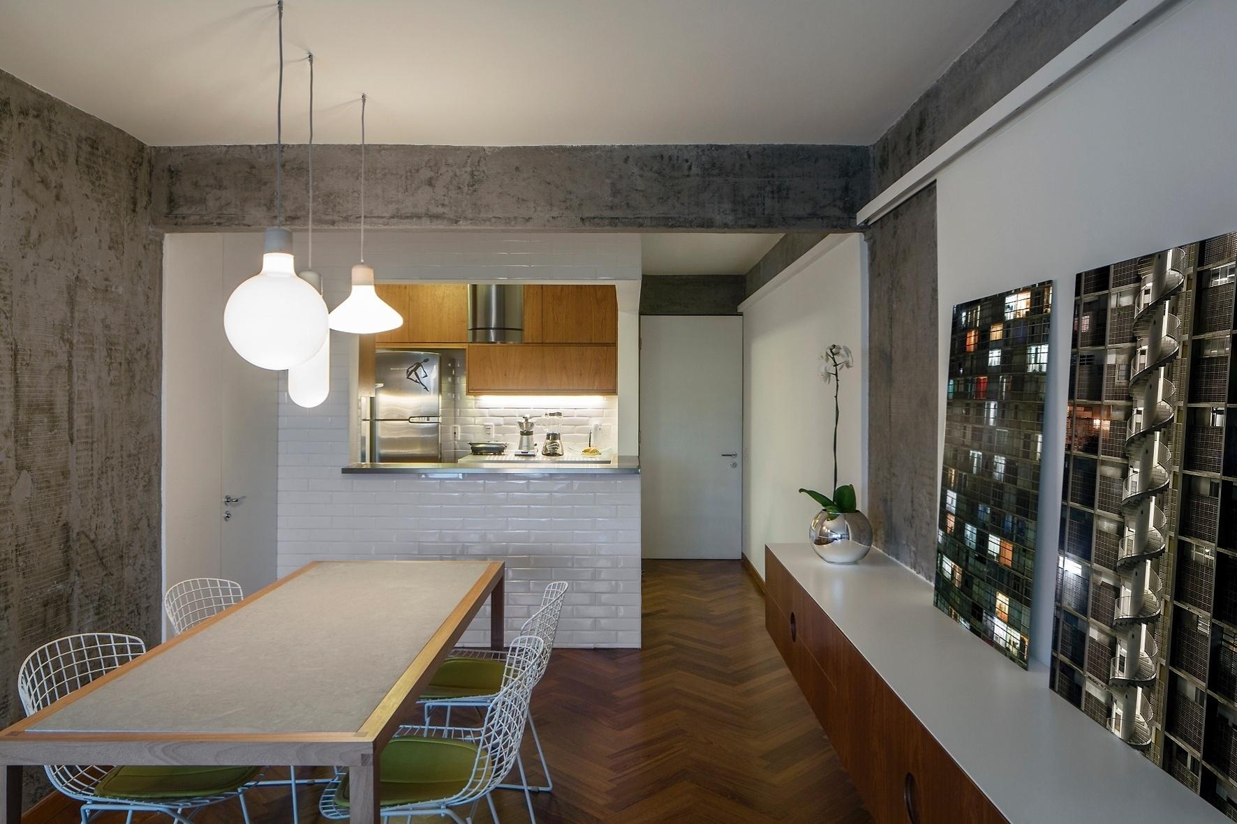 O interior do Apartamento FT, com 98 m², foi totalmente integrado para racionalizar o uso do espaço compartilhado entre moradia e trabalho. A cozinha (ao fundo) tem passa-pratos voltado para o jantar, com bancada em aço-inox (Mekal) e paredes revestidas com azulejos cerâmicos brancos, também presentes na cozinha. A reforma foi projetada pelo escritório Pascali Semerdjian Arquitetos