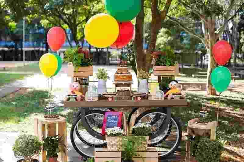 """A hora do parabéns é o momento mais importante da festa, não é à toa que a mesa do bolo é o cantinho predileto dos convidados. O móvel que dá sustentação à decoração junto aos docinhos também pode ser uma peça especial para compor o visual. Cavalete, rodas e até cubos de madeira estão entre as opções de mesas diferentes. A comemoração com tema da """"Turma da Mônica"""", feita pela decoradora Tathyana Abreu (www.tathyanaabreu.com.br), traz quatro rodas grandes na base móvel e palets de madeira - Daniela Ditz/Divulgação"""