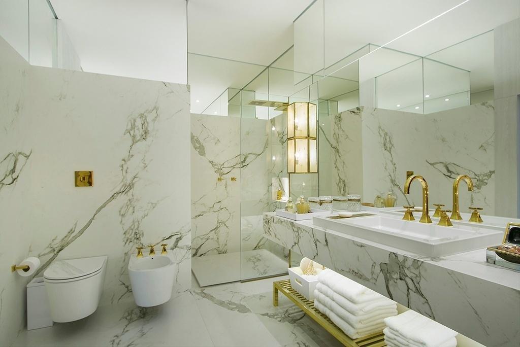 Clássico - Este banheiro, projetado por Paola Ribeiro, tem piso e paredes revestidos por uma superfície composta de minerais naturais ultracompactados com aparência de mármore. O uso extensivo de espelhos, assim como os metais dourados (Deca), dão sofisticação ao ambiente
