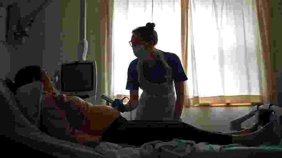 Parteira checa batimentos cardíacos de bebê em mulher grávida durante a pandemia de coronavírus - Hannah McKay/PA Images via Getty Images