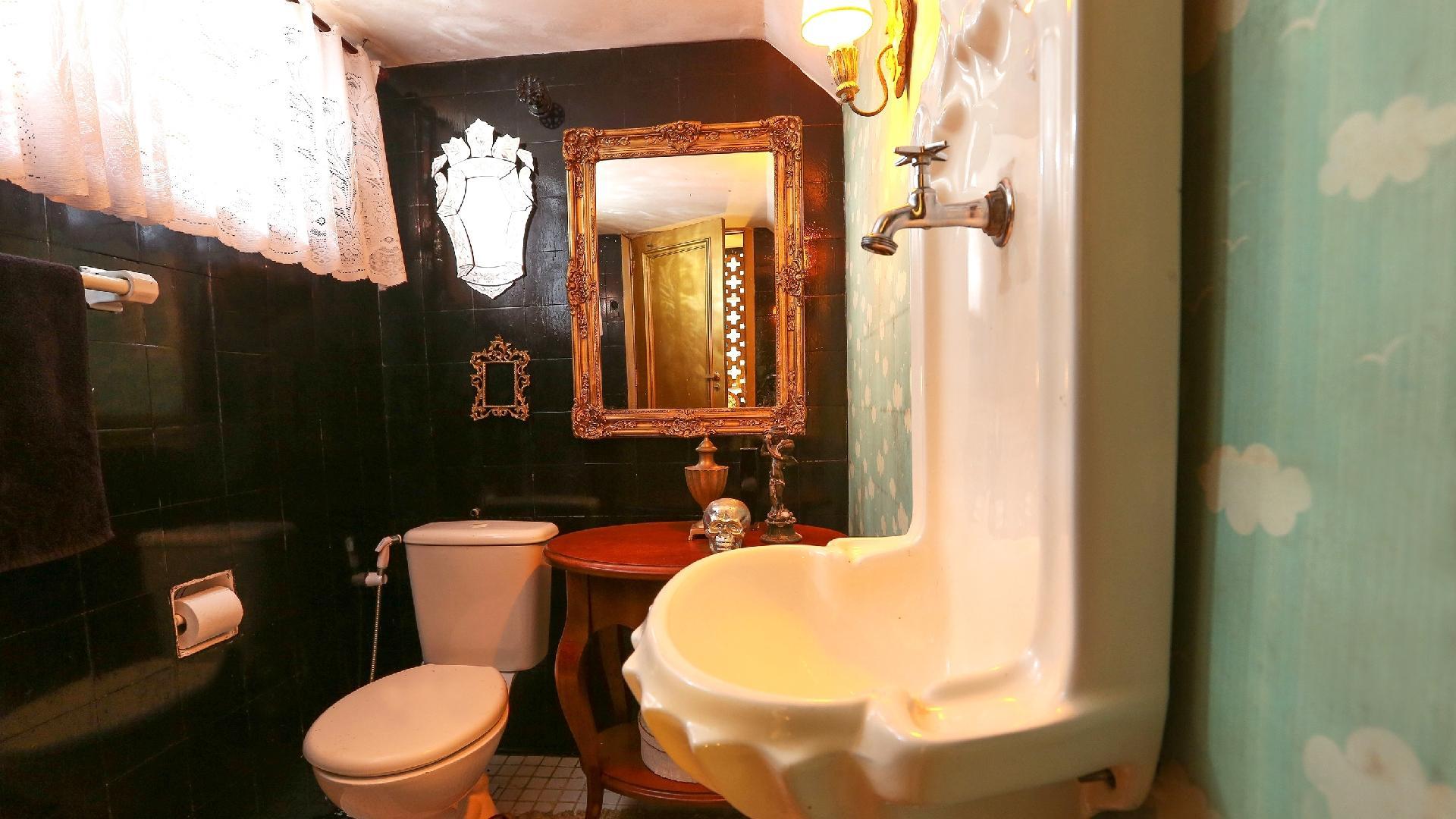 O lavabo da casa de Igor Rickli, no Rio de Janeiro, também foi decorado por ele e pela cantora Aline Wirley. Três espelhos com diferentes dimensões foram posicionados sobre a parede de azulejos pintados. À direita, o lavatório de parede contrasta com o revestimento infantil e delicado, cheio de nuvens e passarinhos: tal combinação leva um clima descontraído ao espaço