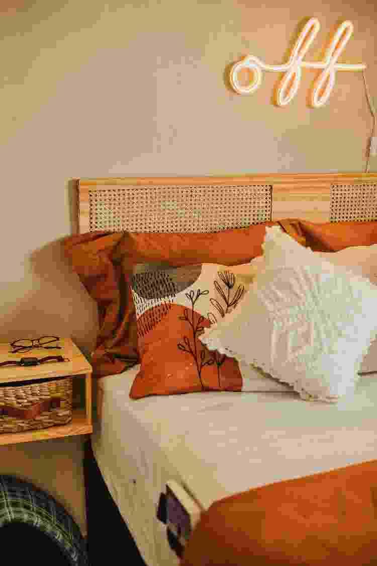 Na parede, uma técnica de pintura lavada; cabeceira nova feita com madeira e palhinha; mesas laterais em madeira. Repare ainda no neon e nos bolsos acoplados ao lençol. - Apto.21 - Apto.21