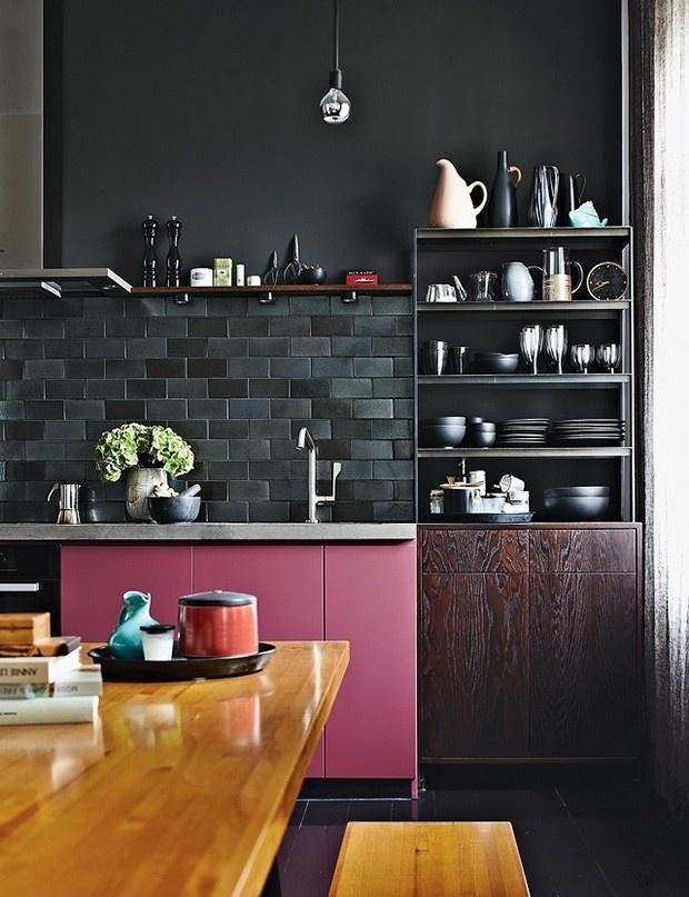 A foto traz uma cozinha preta que tem sua sobriedade quebrada pelo armário rosa. A decoração foi feita por Peter Fehrentz para um apê em Berlim, Alemanha. O arquiteto Maurício Karam analisa a combinação como chique e divertida e aponta as diferentes texturas do preto da cerâmica ao da pintura da parede e acrescenta: