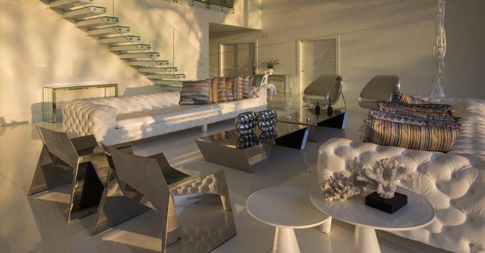 O living projetado pelo arquiteto Léo Shehtman conta com peças esculturais em aço inox, que conferem um toque futurista à decoração baseada em peças e acabamentos brancos. A casa em Campinas (SP) pertence a um jovem casal fãs de design contemporâneo