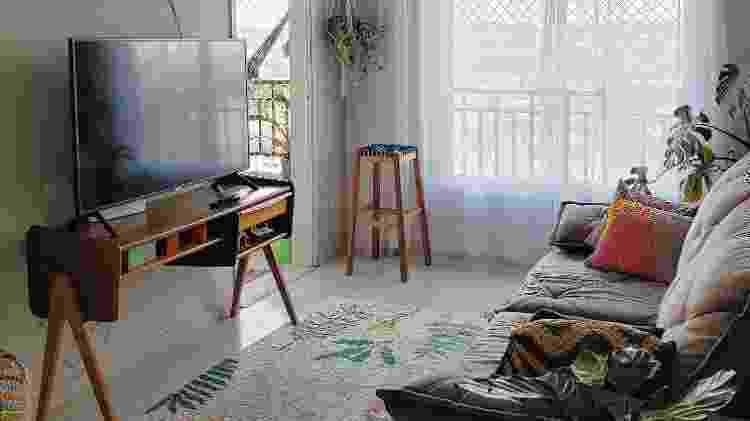 Um tapete traz aconchego e delimita espaço. Deve ser sempre igual ou maior do que a largura do sofá e sair de baixo do sofá até o início do rack - Divulgação @de.aluguel - Divulgação @de.aluguel