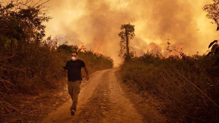 Homem foge de incêndio florestal  na zona rural de Pocone, Mato Grosso, Brasil, em agosto de 2020 - Gustavo Basso-NurPhoto/Getty Images