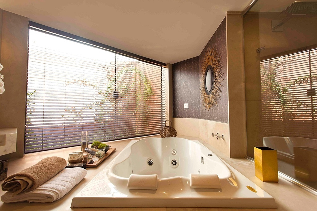 Spa - Projetado pela arquiteta Denise Monteiro, esse banheiro foi concebido para funcionar como área de meditação e relaxamento e tem vista para o jardim externo, quando a persinada (à esq.) está aberta. Destacam-se no ambiente: a banheira de hidromassagem, a paleta de beges e marrons  não agressivos e alguns detalhes, como o espelho em formato de sol e o papel de parede vinílico