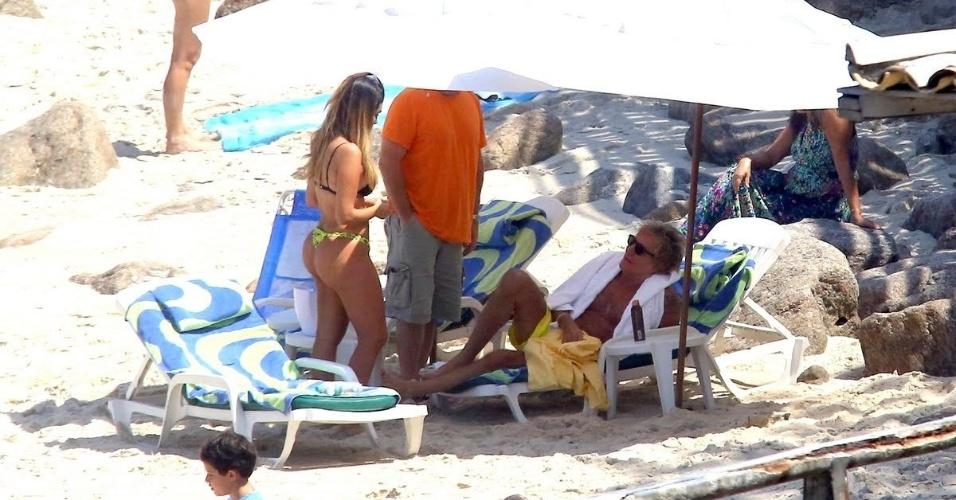 21.set.2015 - Rod Stewart aproveitou o dia de sol para curtir uma praia nesta segunda-feira, no Rio de Janeiro. Debaixo da barraca, o cantor que se apresentou em São Paulo e no Rock in Rio conversou com uma morena