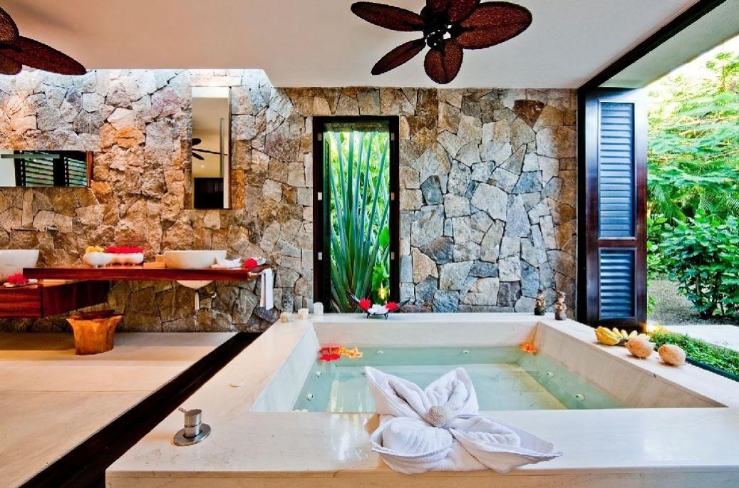 Se dinheiro não é problema, que tal este banheiro em Nayarit, México? A diária de um quarto custa R$ 7.222 e conta com banheira de hidromassagem com vista para um belo jardim, duas cubas espaçosas e brancas e dois ventiladores de teto em forma de flores. A parede de pedras deixa o banheiro com cara de rústico
