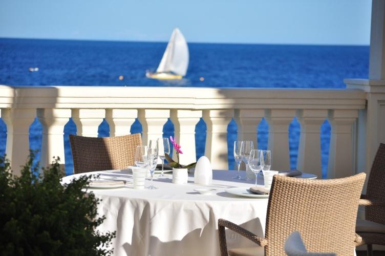No verão é possível jantar no ambiente externo do restaurante Blue Bay, com vista para o mar Mediterrâneo