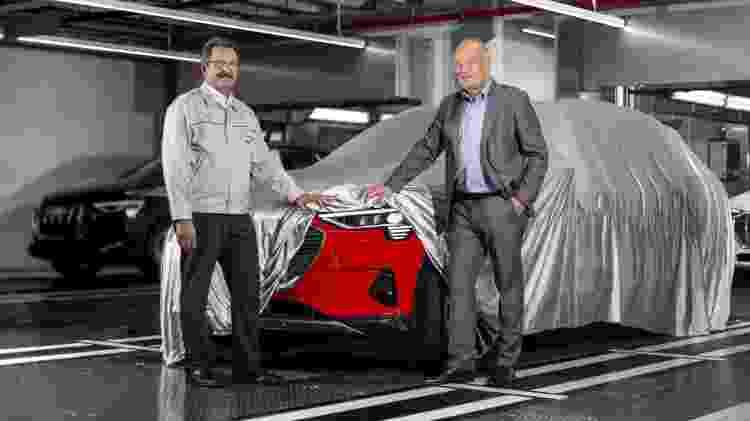 Executivos da Audi fazem segredinho com um e-tron real (vermelho), mas deixam escapar um e-tron descoberto ao fundo (preto). Modelo está pronto, sendo fabricado e surge em duas semanas - Divulgação