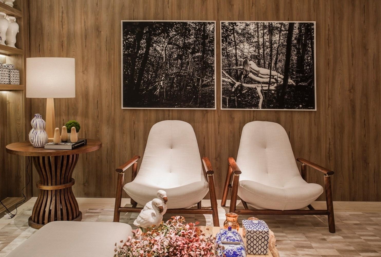 As paredes do estar da Casa de Praia foram revestidas com porcelanato que imita madeira. Para combinar com o revestimento neutro, a arquiteta Vanessa Martins escolheu um par de poltronas