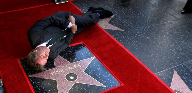 O ator Hugh Laurie brinca deitado ao lado de sua estrela na Calçada da Fama durante sessão de fotos - Mario Anzuoni / Reuters