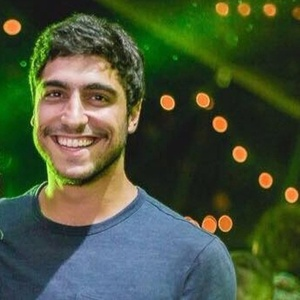 Thiago Magalhães é moreno, tem cabelos curtos e sorri, usando camiseta azul