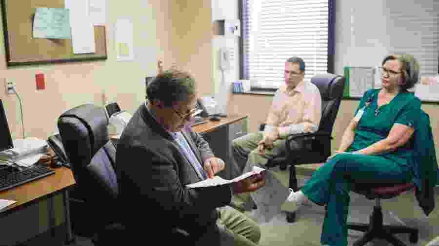 O especialista em câncer Oliver Sartor analisa as anotações dos pacientes com o Dr. Brian Lewis e Mary Livaudais, uma enfermeira, em seu consultório no Tulane Medical Center, em Nova Orleans - Annie Flanagan / The New York Times