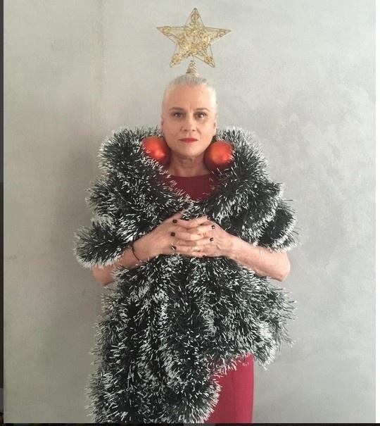 """24.dez.2015 -Vera Holtz resolveu desejar Boas Festas aos amigos de uma maneira bem criativa. Nesta quinta-feira (24), ela se se fantasiou de árvore de Natal, com  brincos de bolas vermelhas, festões verdes e estrela dourada na cabeça e publicou a foto em suas redes sociais: """"Optei por esse"""", escreveu a atriz sobre o modelo escolhido na legenda"""