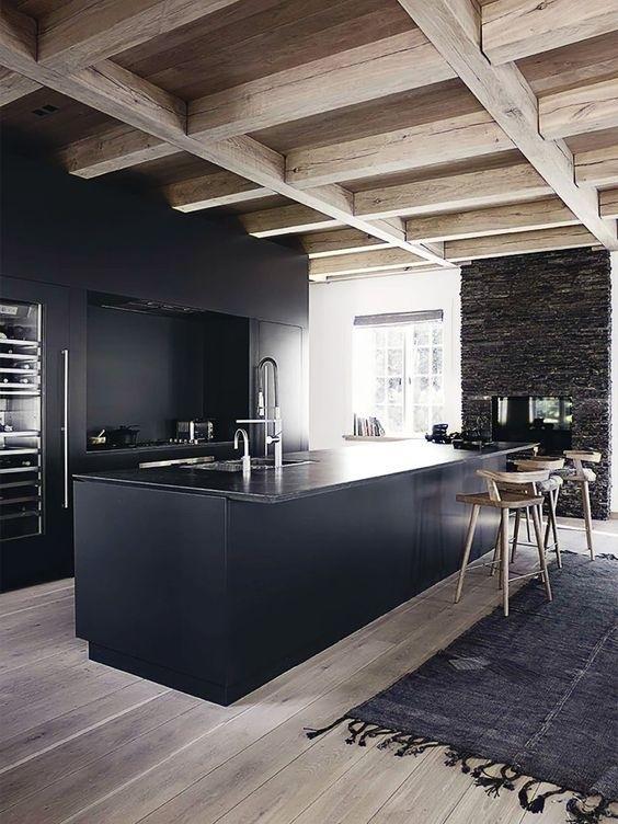 A madeira clara é usada como contraponto ao preto das paredes e dos gabinetes da cozinha. Neste exemplo, a madeira apresenta-se em seu estado rústico, na estrutura do telhado.