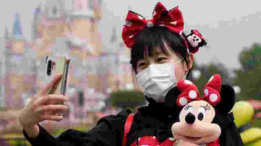 Visitante vestida de Minnie e usando máscara de proteção contra o coronavírus tira selfie na reabertura da Disney de Xangai, na China - Aly Song/Reuters