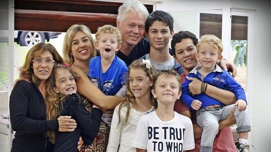 No sentido anti-horário, Edson Kemper, a mulher, Daniela Finotti, a ajudante da família, Naná, e os sete filhos - Arquivo pessoal
