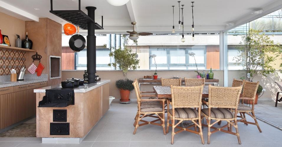 Na área de lazer de uma cobertura dúplex na Vila Madalena, em São Paulo, o elemento central da cozinha gourmet é o fogão a lenha feito com cimento e ferro fundido. O apartamento foi projetado pela decoradora Solange Medina, para um casal de meia-idade, que tem a culinária como
