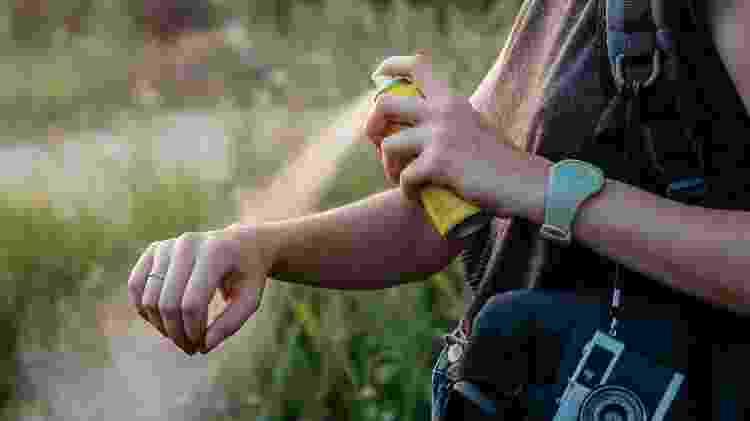 Mulher passando repelente no braço - Photoboyko/IStock - Photoboyko/IStock