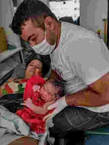 Michaella Mignone, após o parto, com o bebê e um socorrista - Arquivo pessoal