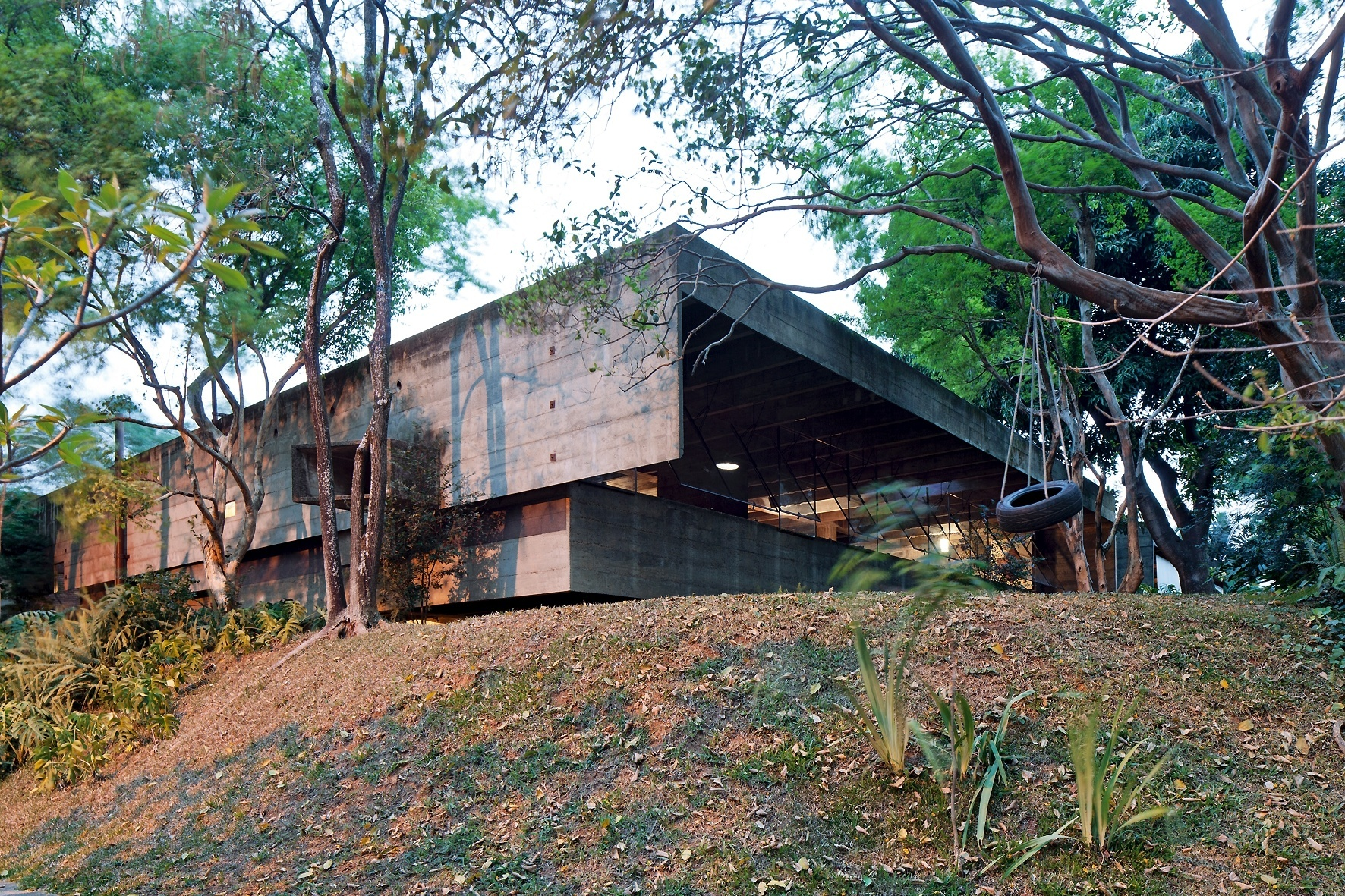 Dois planos sobrepostos definem a empena cega do pavimento superior da casa Butantã, projetada pelo arquiteto Paulo Mendes da Rocha. Em primeiro plano, vê-se o talude e o balanço de pneu improvisado para os netos do arquiteto