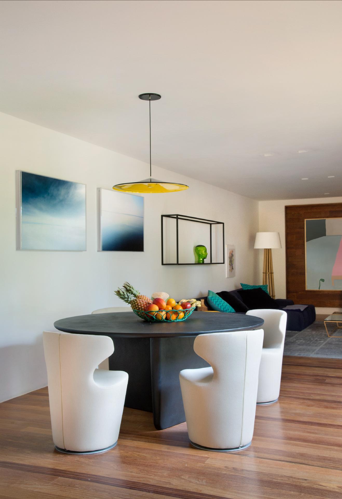 Integrada com a sala de TV (ao fundo), a área de jantar conta com a mesa Tobi Ishi e as cadeiras giratórias Mini Papilio, ambas da B&B Italia. O arquiteto Otto Felix decorou a parede do ambiente com as fotografias de Vane Barini
