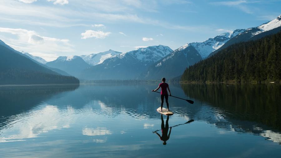 Mulher stand-up paddle embarcando em um lago de montanha intocada - Getty Images