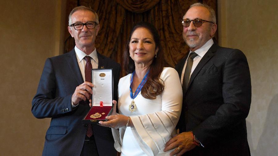 Gloria Estefan recebe medalha de ouro das artes do governo da Espanha das mãos do ministro da Cultura e Esportes Jose Guirao. À sua direita, o marido Emilio Estefan - PIERRE-PHILIPPE MARCOU/AFP