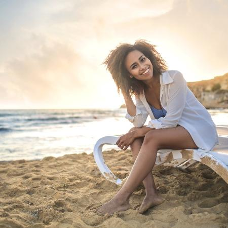 Mulher negra na praia; mar - iStock