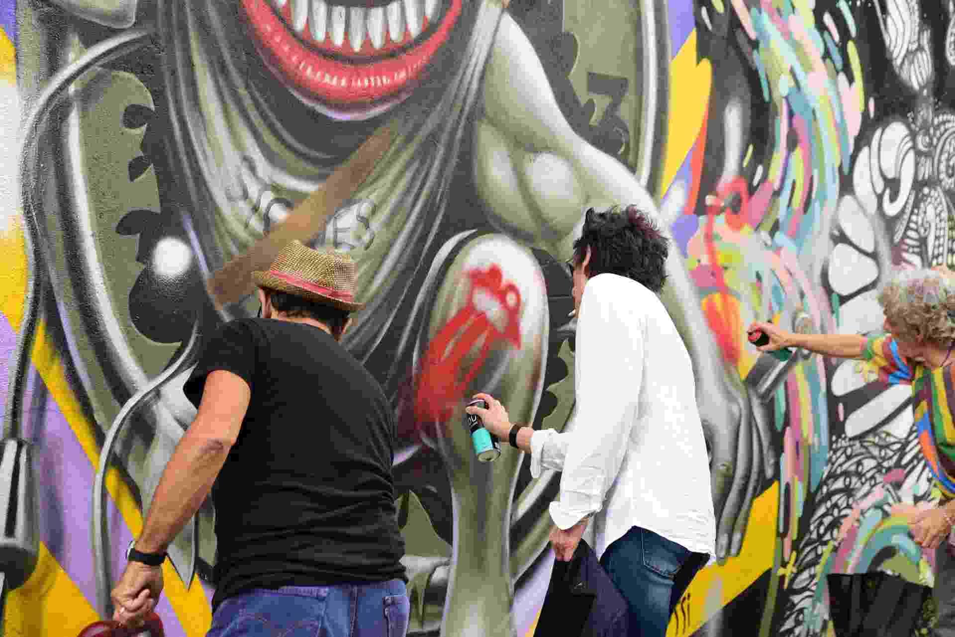 23.fev.2016 - O guitarrista Ron Wood grafita boca do Rolling Stones no Beco do Batman, em São Paulo - Leo Franco/AgNews