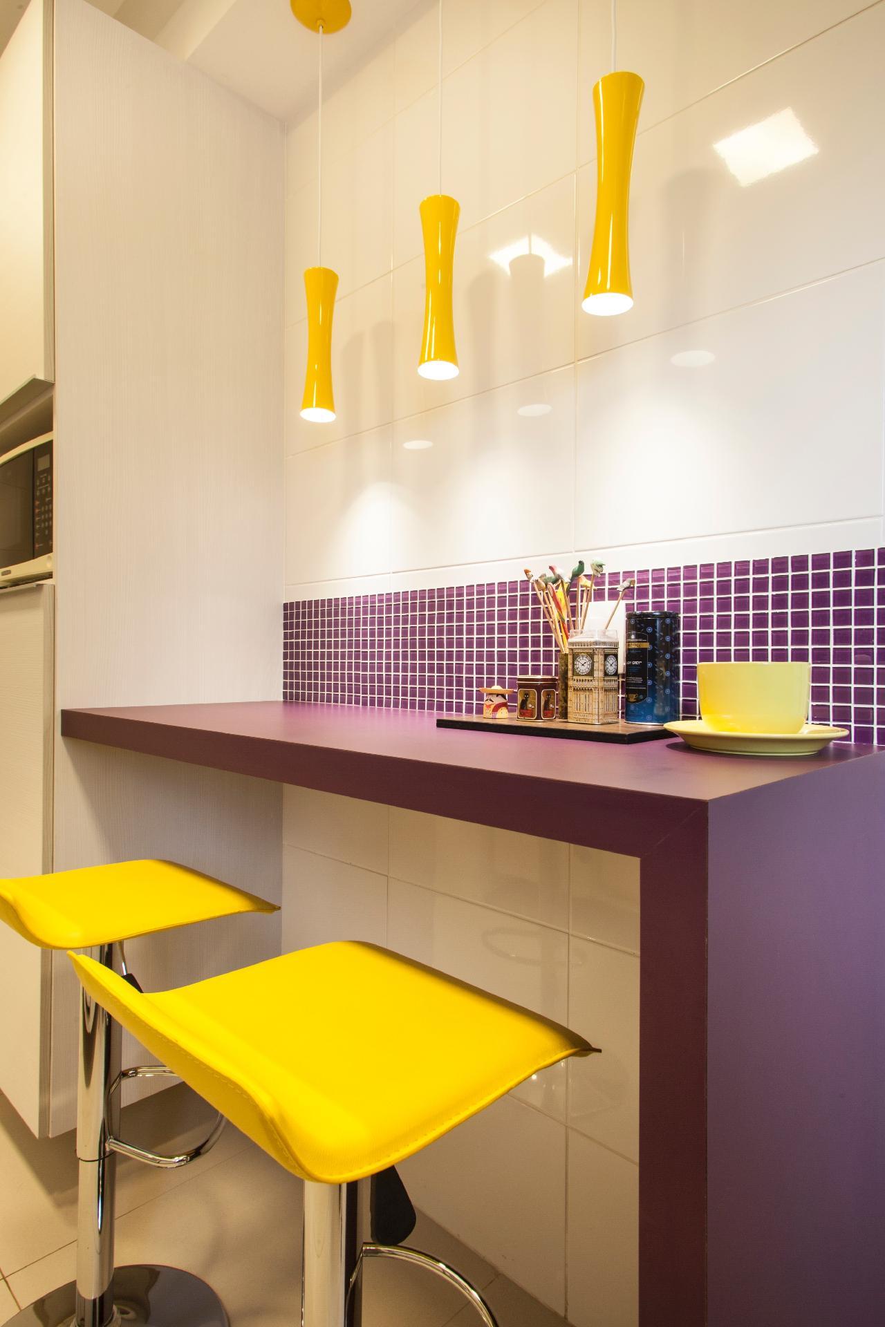 É possível criar um espaço divertido para refeições a dois brincando com cores fortes e diferentes revestimentos. Neste ambiente assinado pelas arquitetas Luciana Correa e Elaine Delegredo, roxo e amarelo se alternam nas banquetas, bancada,  pendentes e objetos